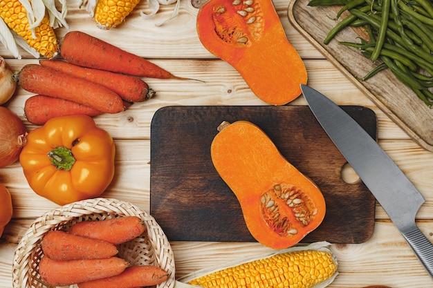 Вид сверху тыквы, моркови и кукурузы на коричневый деревянный стол