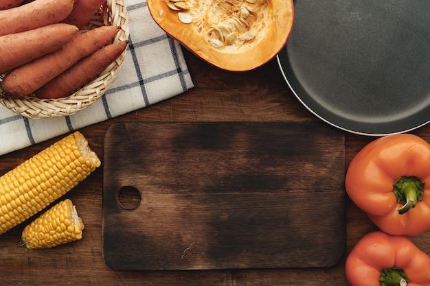 茶色の木製テーブルの上のカボチャ、ニンジン、トウモロコシの上面図