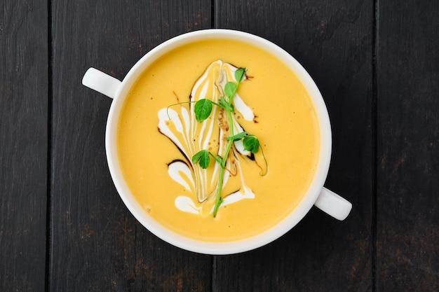 Вид сверху тыквенного супа-пюре с соусом барбекю и сметаной