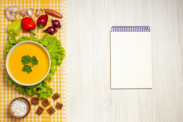 白いテーブルの上の野菜とカボチャスープの上面図