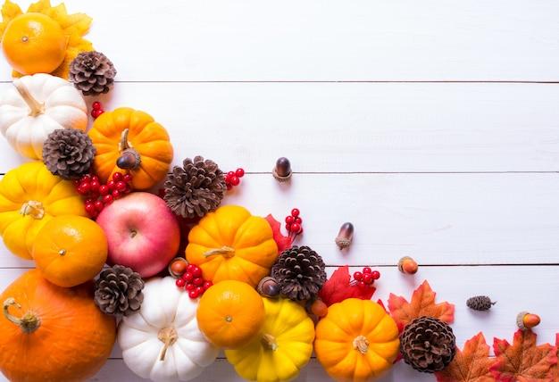 Вид сверху тыквы, красные ягоды и сосновые шишки