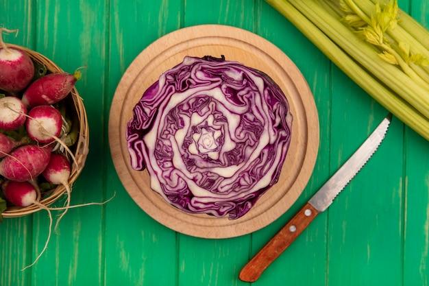 Вид сверху фиолетовой капусты на деревянной кухонной доске с ножом с редисом на ведре с сельдереем, изолированным на зеленой деревянной стене