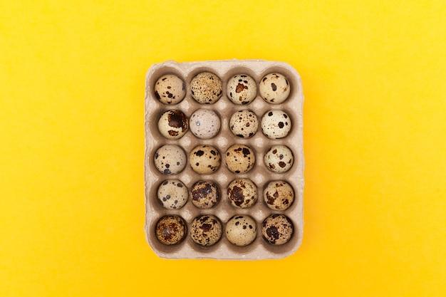 黄色の背景に分離されたパッケージのウズラの卵の上面図