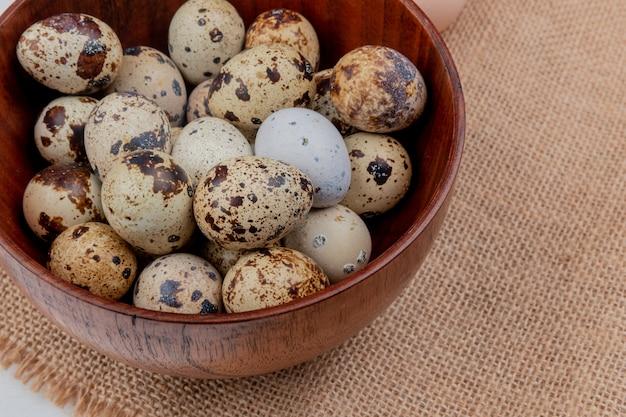 Вид сверху перепелиных яиц на деревянной миске на фоне ткани мешка