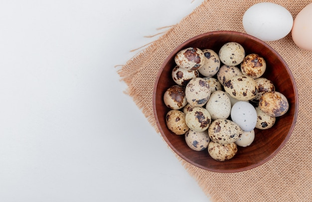 Вид сверху перепелиных яиц на деревянной миске на мешковине с куриными яйцами на белом фоне