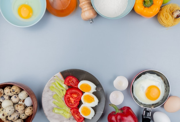 コピースペースと白い背景の上のフライパンで目玉焼きとトマトのスライスを皿に半熟卵を木製のボウルにウズラの卵の平面図