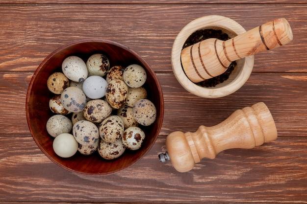 木製の背景に木造乳鉢と乳棒と木製のボウルにウズラの卵のトップビュー