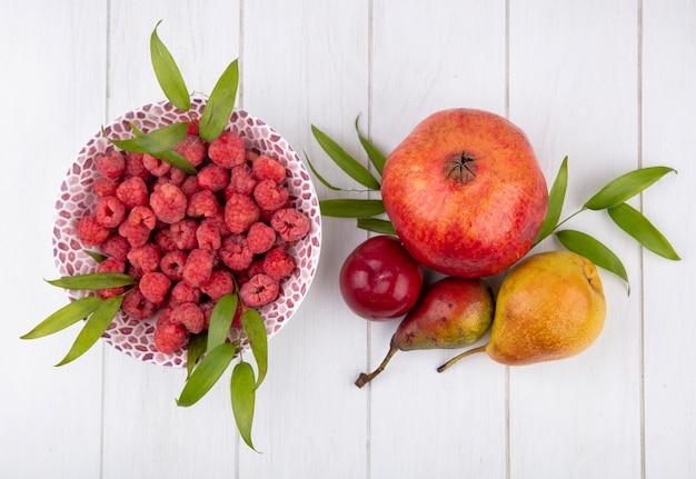 Вид сверху малины и листьев в миску и граната сливы персики на деревянной поверхности