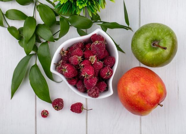 Вид сверху малины в миске с цветными яблоками и веткой на белой поверхности