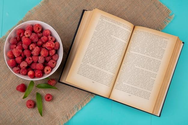 Вид сверху малины в миску и открытой книги с листьями на вретище и синей поверхности
