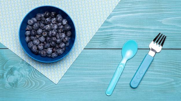 Вид сверху малины в миске для детского питания со столовыми приборами