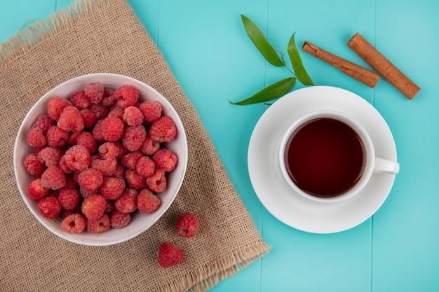 Вид сверху малины в миску на вретище и чашка чая на блюдце с корицей и листьями на синей поверхности