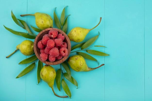 Вид сверху малины в миску с персиками и листьями на синей поверхности