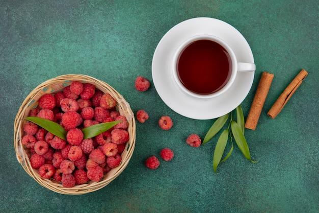 Вид сверху малины с листьями в корзине и чашка чая на блюдце с корицей и листьями на зеленой поверхности