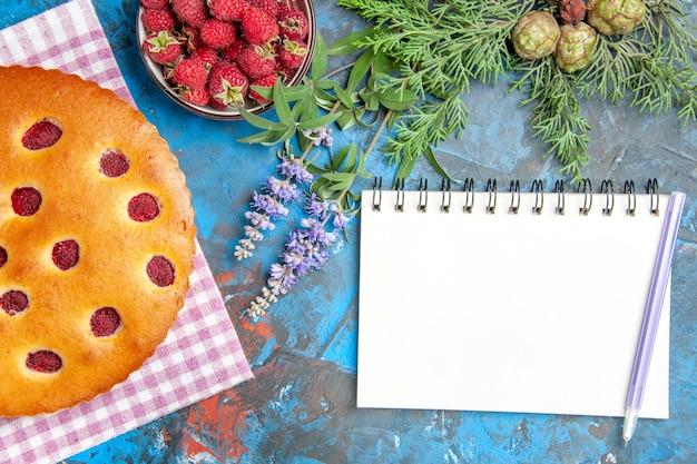 青い表面にラズベリー松の木の枝のノートブックとキッチンタオルボウルのラズベリーケーキの上面図