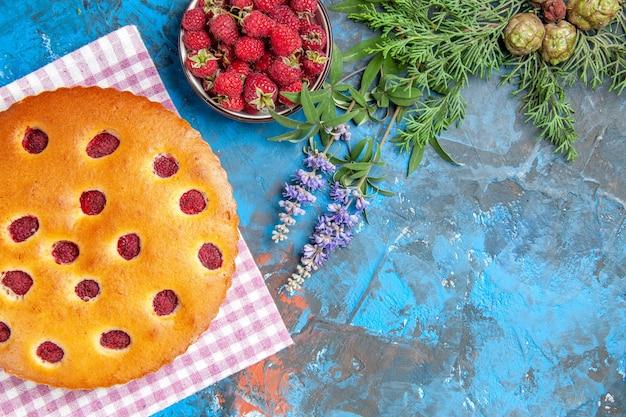 青い表面にラズベリー松の木の枝とキッチンタオルボウルのラズベリーケーキの上面図 無料写真