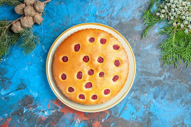 青い表面のプレートコーン上のラズベリーケーキの上面図