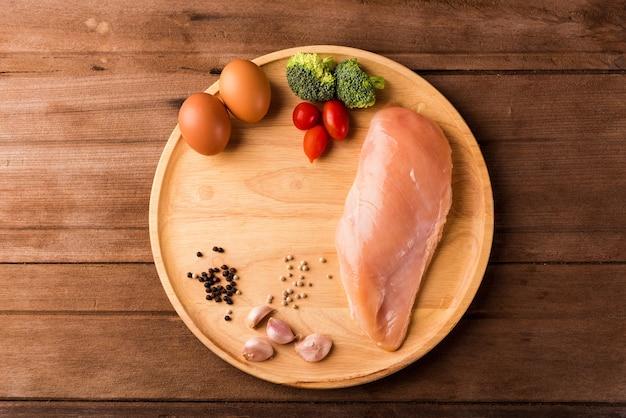 生の鶏の胸肉の切り身の上面図ローズマリーとプレートウッドの卵で骨なし