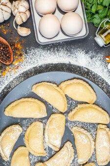 周りに小麦粉と黒いテーブルに卵が落ちたオイルボトルニンニクコショウと灰色のプレート上の生餃子の上面図