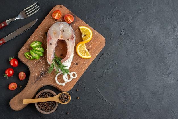 黒の苦しめられた表面の右側に設定された木の板カトラリーの生の魚と新鮮なみじん切り野菜レモンスライススパイスの上面図