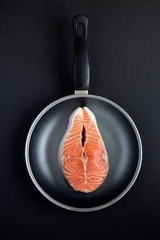 黒の背景にフライパンで生の魚のサーモンの上面図。閉じる。場所は垂直です。