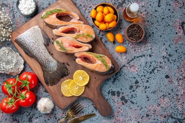 木製のまな板に生の魚レモンスライス緑コショウと青黒の色のテーブルに食べ物の花の上面図