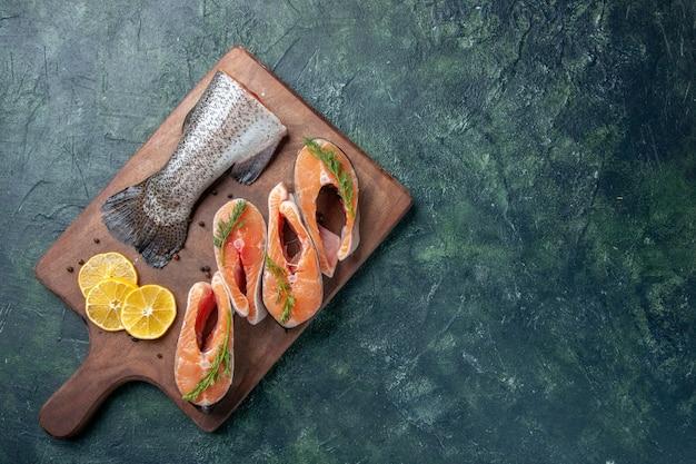 暗いテーブルの上の木製のまな板に生の魚レモンスライス緑コショウの上面図
