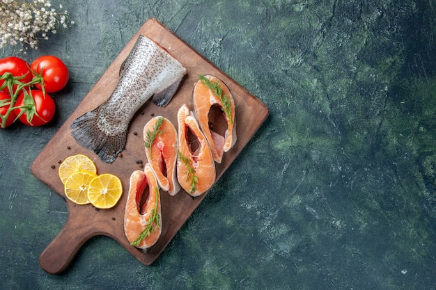 暗いテーブルの上の木製のまな板トマトの生の魚レモンスライス緑コショウの上面図