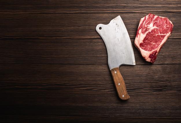 テキスト用のスペースと木製の背景に素朴な肉切り包丁と生の新鮮な大理石の肉ステーキリブアイの上面図。ジューシーなオーガニックステーキや肉屋のコンセプトを調理し、健康的なきれいな食事、クローズアップ