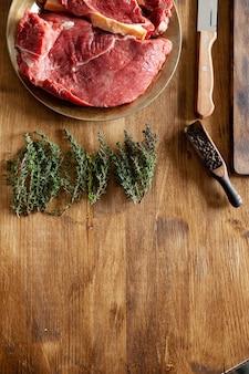 Вид сверху сырого свежего мяса рядом с зеленым розмарином, перцовыми бобами и ножом шеф-повара. кухонный стол.
