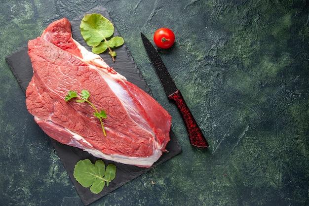 Вид сверху сырого свежего красного мяса и зелени на разделочной доске, нож, помидор на зеленом черном фоне цветов