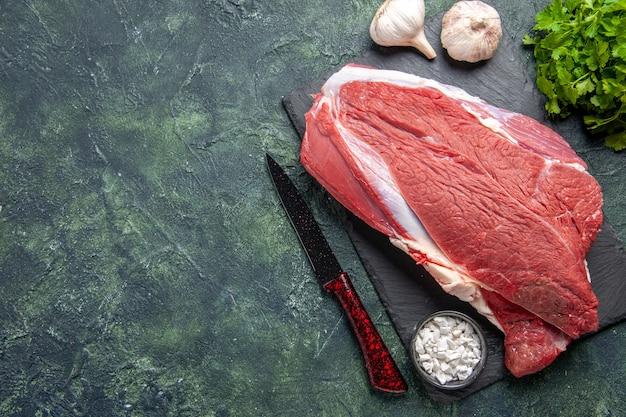 緑黒ミックス色の背景の左側のまな板に生の新鮮な赤身の肉と塩緑のバンドルナイフの上面図