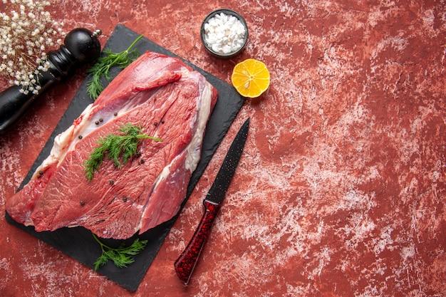Вид сверху сырого свежего красного мяса с зеленым и перцем на черной доске, нож, деревянный молоток, соль, лимон, на масляном пастельном красном фоне со свободным пространством