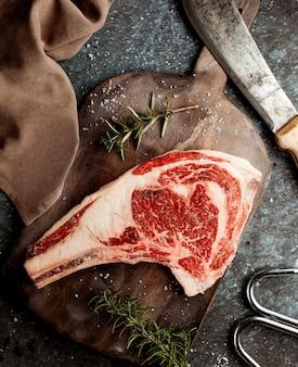 소금으로 장식 된 원시 양고기 허벅지 조각의 상위 뷰