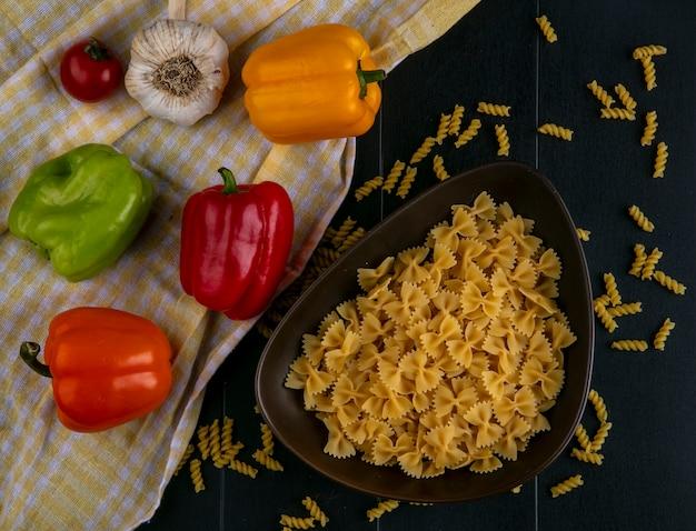 Вид сверху сырых макарон в миске с цветным болгарским перцем на желтом клетчатом полотенце с чесноком на черной поверхности