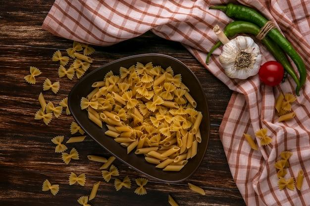 Вид сверху сырой пасты в миске с чесночным помидором и перцем чили на клетчатом полотенце на деревянной поверхности