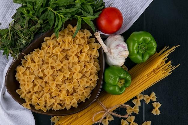 Вид сверху сырых макарон в миске со спагетти, помидорами, чесноком и болгарским перцем с мятой на белом полотенце на черной поверхности