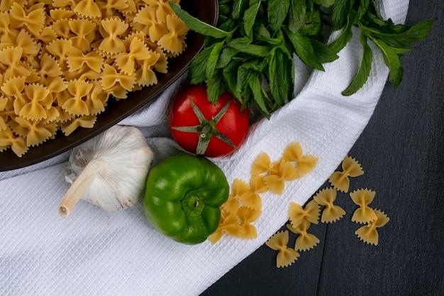 Вид сверху сырой пасты в миске с помидорами, чесноком и болгарским перцем с мятой на белом полотенце на черной поверхности