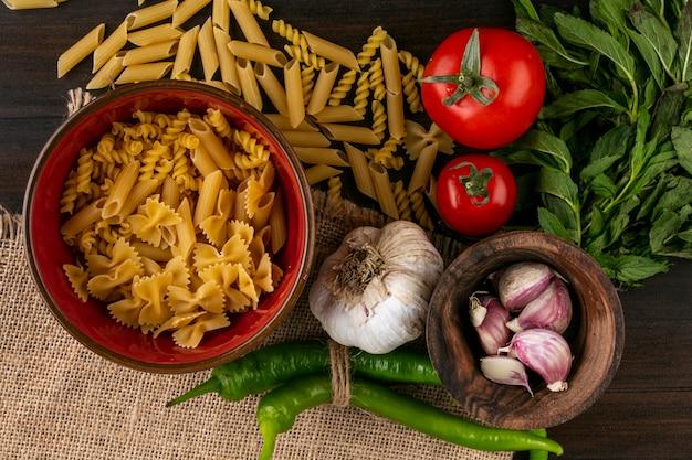 Вид сверху сырой пасты в миске с помидорами, чесноком, перцем чили и пучком мяты на бежевой салфетке