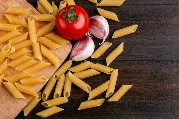 Вид сверху сырых макарон на разделочной доске с помидорами и чесноком на деревянной поверхности