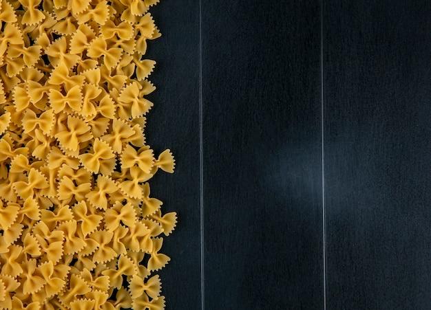 Вид сверху сырых макарон на черной поверхности