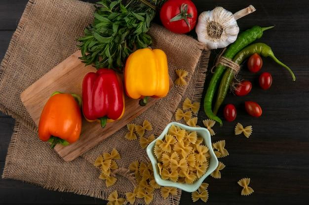 Вид сверху сырых макарон с цветным болгарским перцем на разделочной доске с чесноком, помидорами, перцем чили и мятой на бежевой салфетке