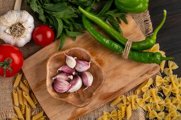Вид сверху сырых макарон с чесноком и перцем чили на разделочной доске с помидорами и пучком мяты на бежевой салфетке