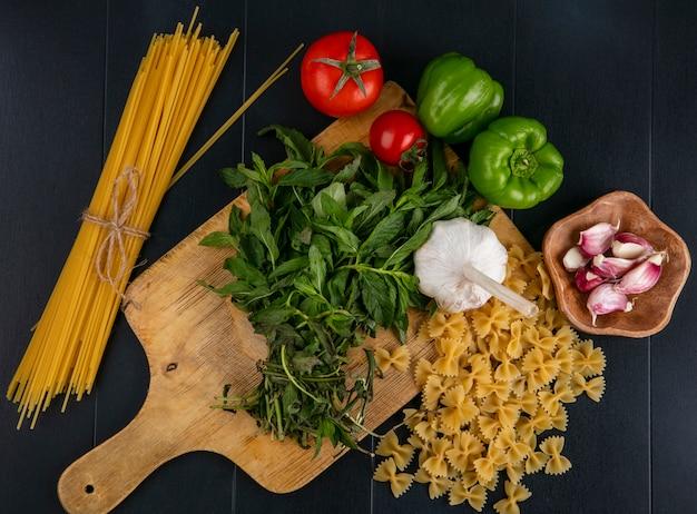 Вид сверху сырых макарон с чесноком, помидорами спагетти и болгарским перцем с мятой на разделочной доске на черной поверхности