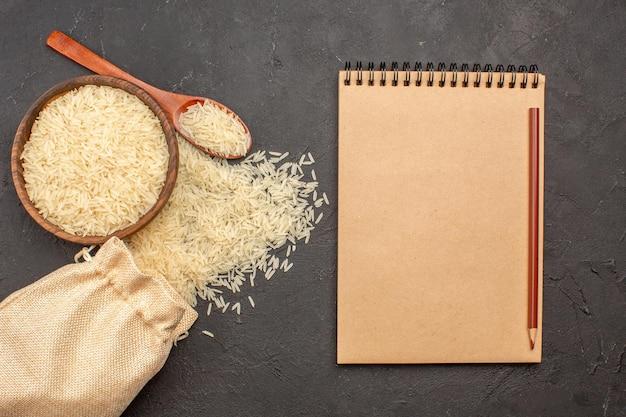 灰色の表面の茶色のプレート内の生米の上面図