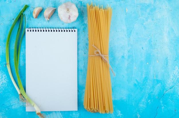 Вид сверху сырых спагетти, перевязанных веревкой, чесноком и зеленым луком с копией пространства на синем фоне