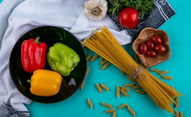 ターコイズブルーの表面にベル色のピーマントマトとニンニクの生スパゲッティのトップビュー