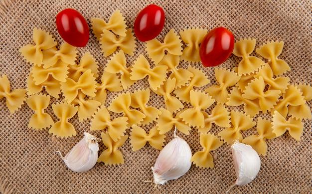 Вид сверху сырых спагетти с помидорами черри и чесноком на бежевой салфетке