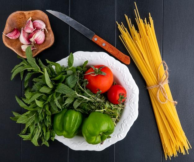 Вид сверху сырых спагетти с мятой, помидорами и болгарским перцем в тарелке с ножом и чесноком на черной поверхности