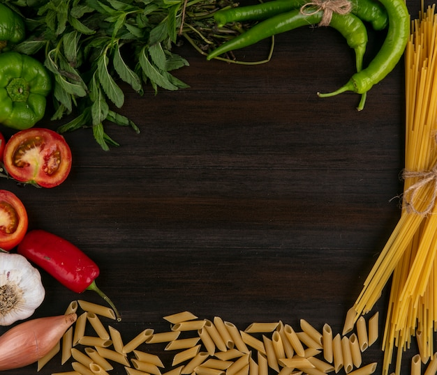 Вид сверху сырых спагетти с макаронами, помидорами, болгарским перцем и чесноком с мятой на деревянной поверхности